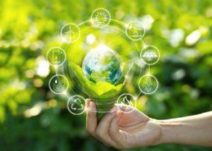 Käsi pitelee vihreää maapalloa.